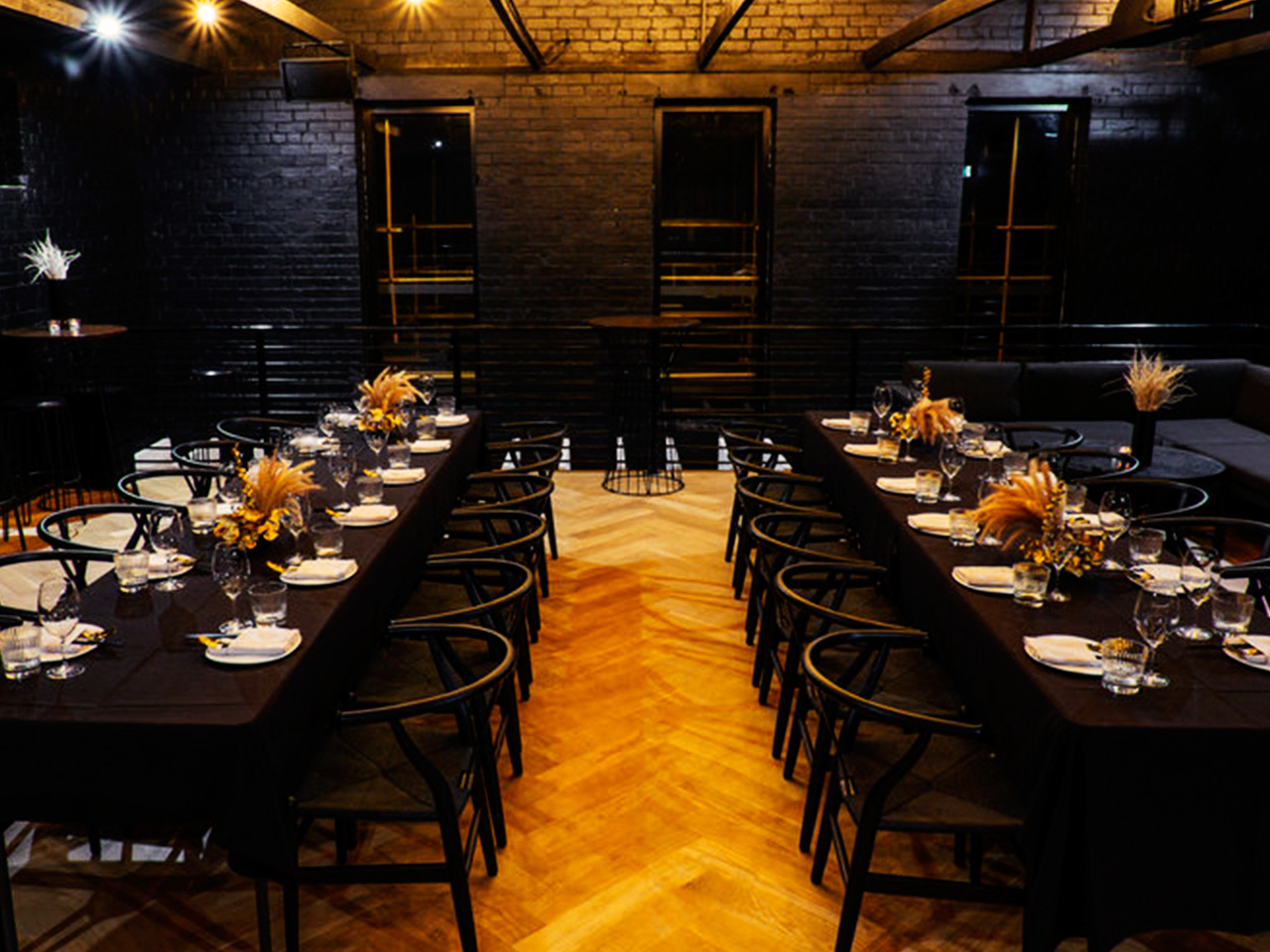Long Tables And Chairs Setup For An Event With Warm Lights Inside The Unique Dark Function Room