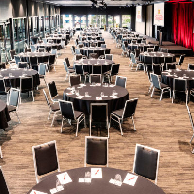 Tables And Chairs In Banquet Style For A Corporate Event Inside The Function Room With Multiple Projection Screen