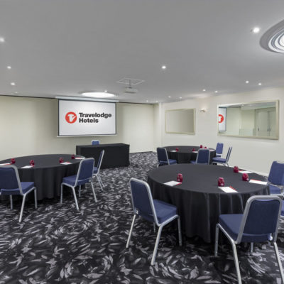 Meeting room with round tables and projector screen