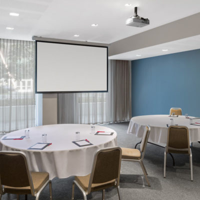 Empty conference room set up with round tables and chairs and projector screen