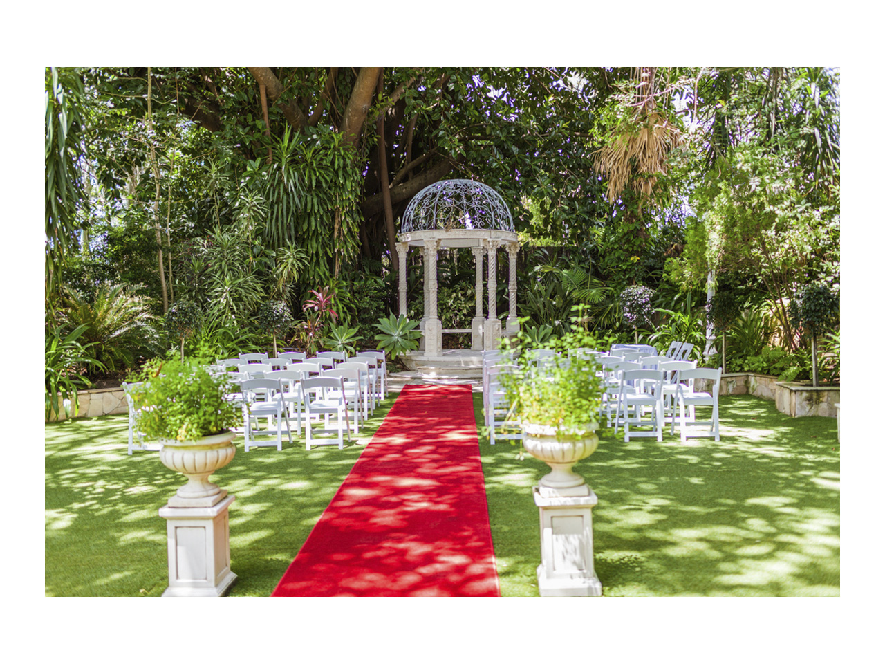 Garden gazebo set for a wedding with red carpet and rows of white chairs either side