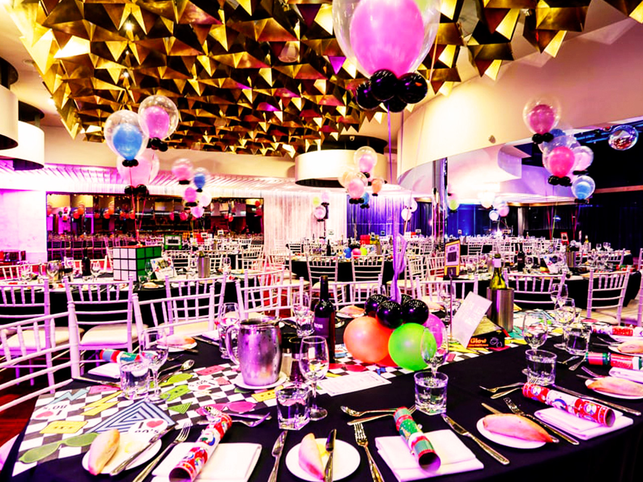 Black tables set for an event with balloons decorating each table