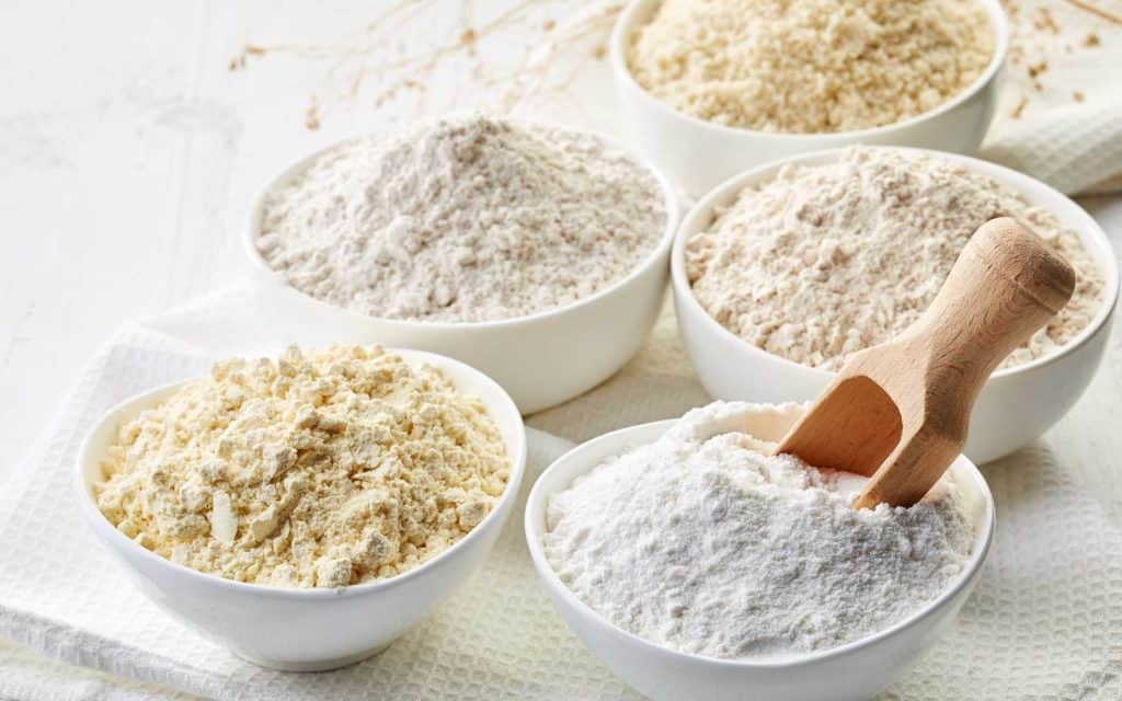 Sample of various gluten-free flours in ceramic bowls with a scoop