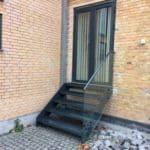 Udendørs ståltrappe med glas fra boligen til terrassen