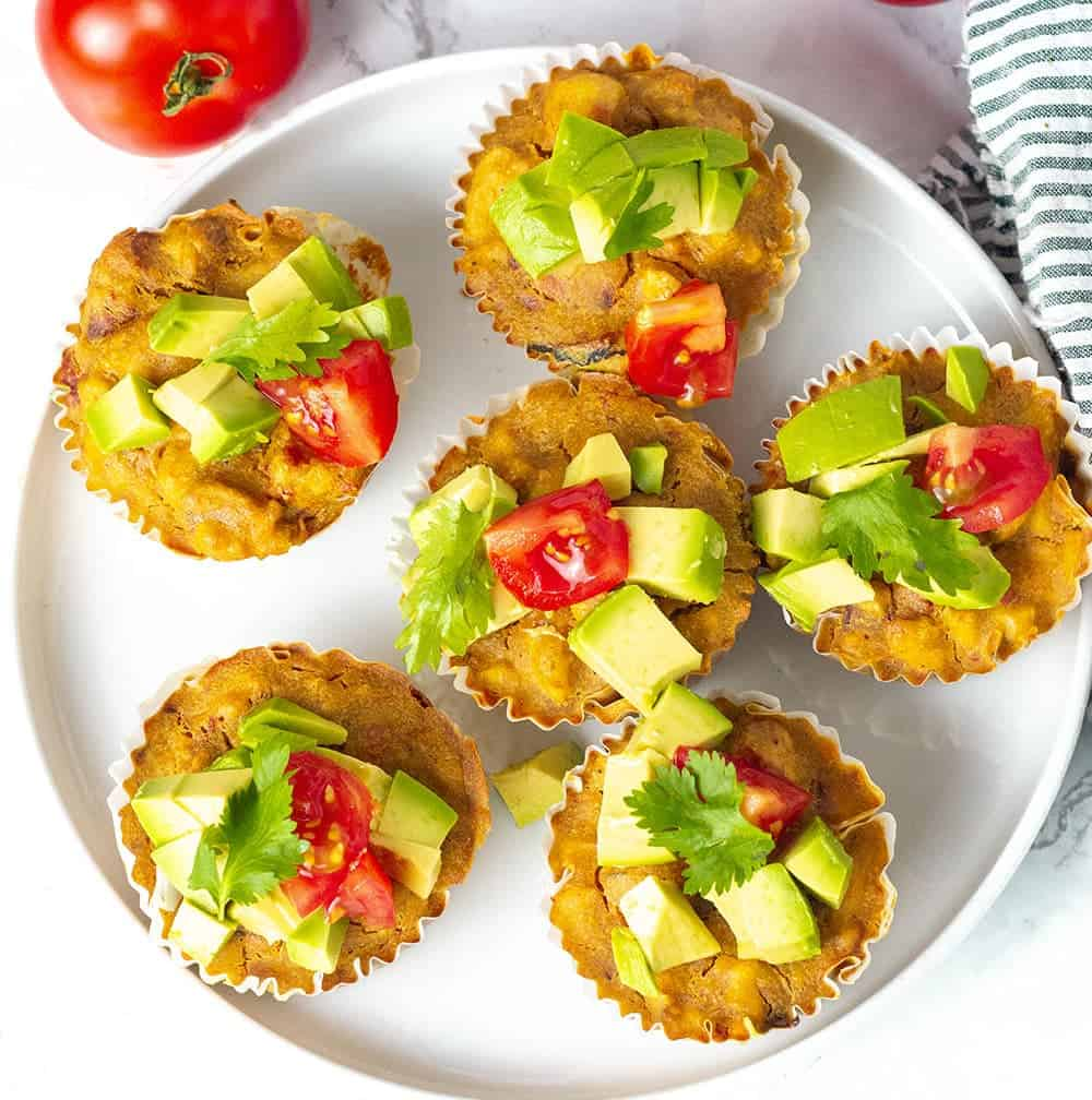 Overlay vegan ackee quiche recipe topped with avocado tomato and cilantro on a white plate with tomatoes on the vine