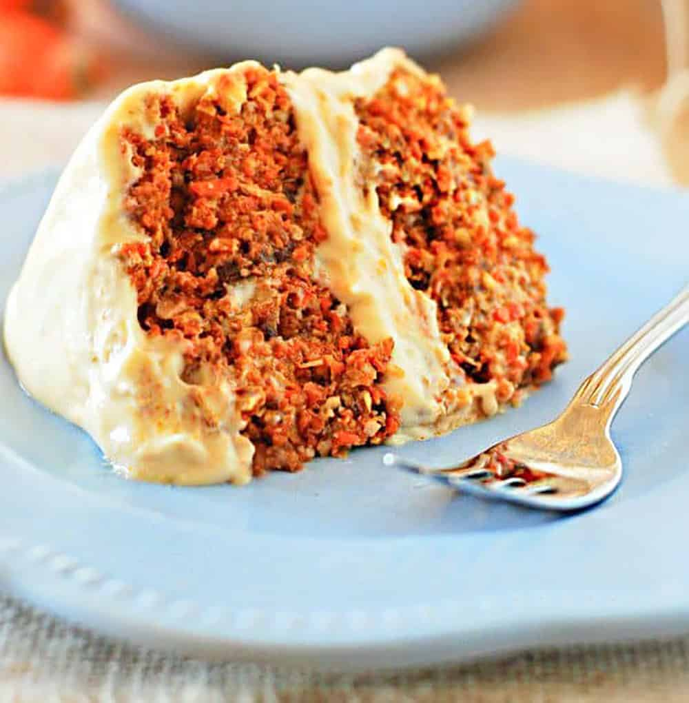 Easy Raw Carrot Cake With Cream Cheese Frosting. slice on a blue plate