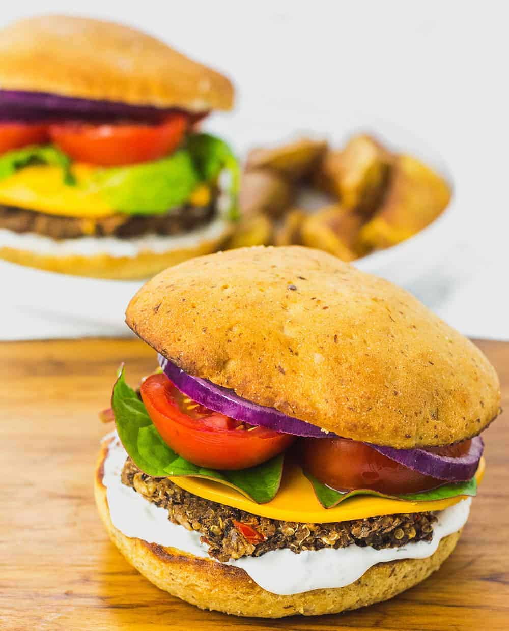Two Black Bean Quinoa Burgers with lettuce, tomato, onion, and fries