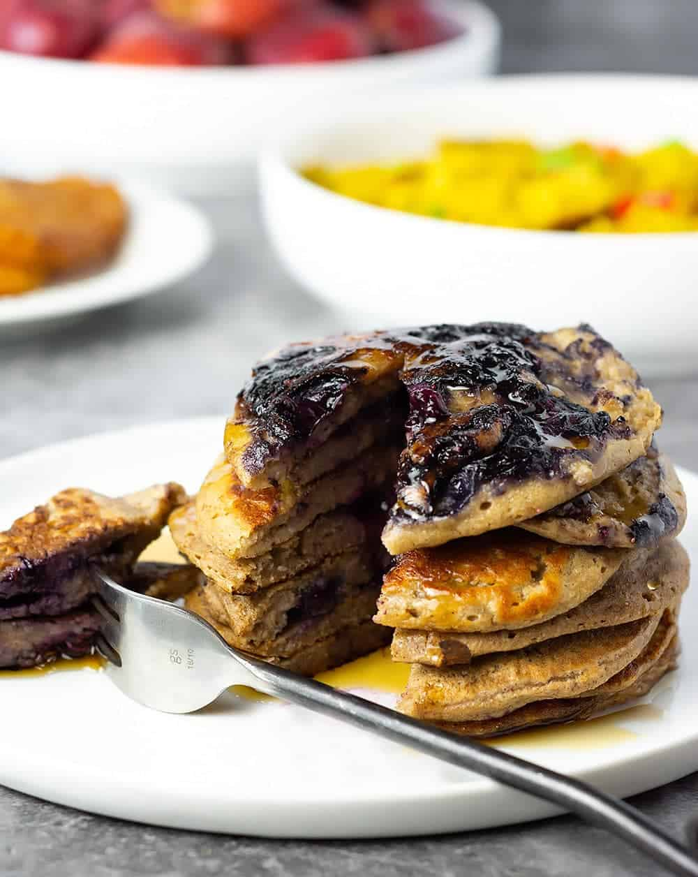 Cut through Banana Blueberry Pancakes on a white plate with a marbled background