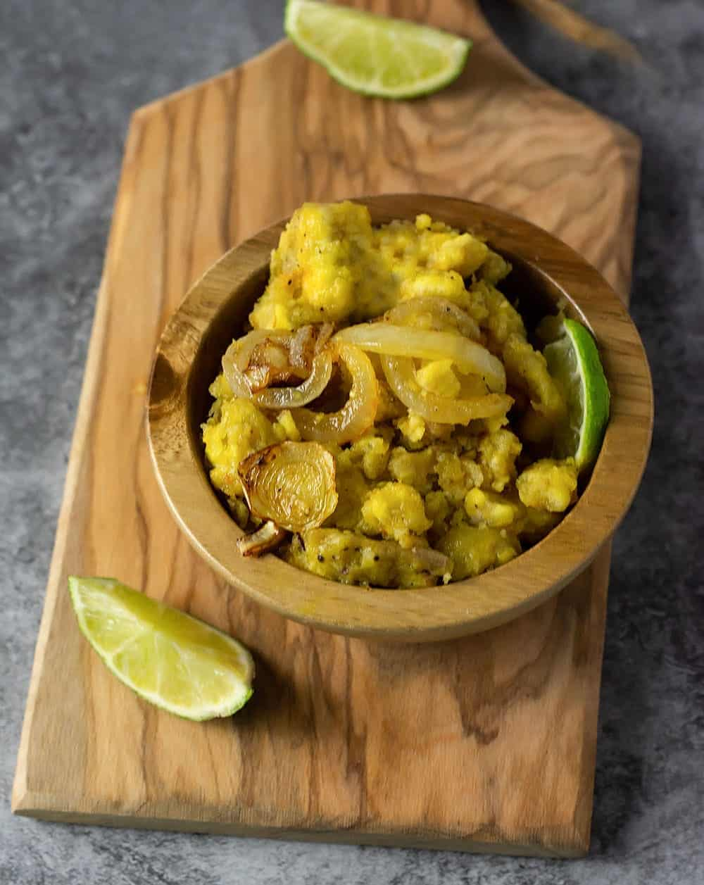 Mangu recipe dominican mashed plantains in a wooden bowl on a wooden cutting board with lime slices on a marbled background overlay