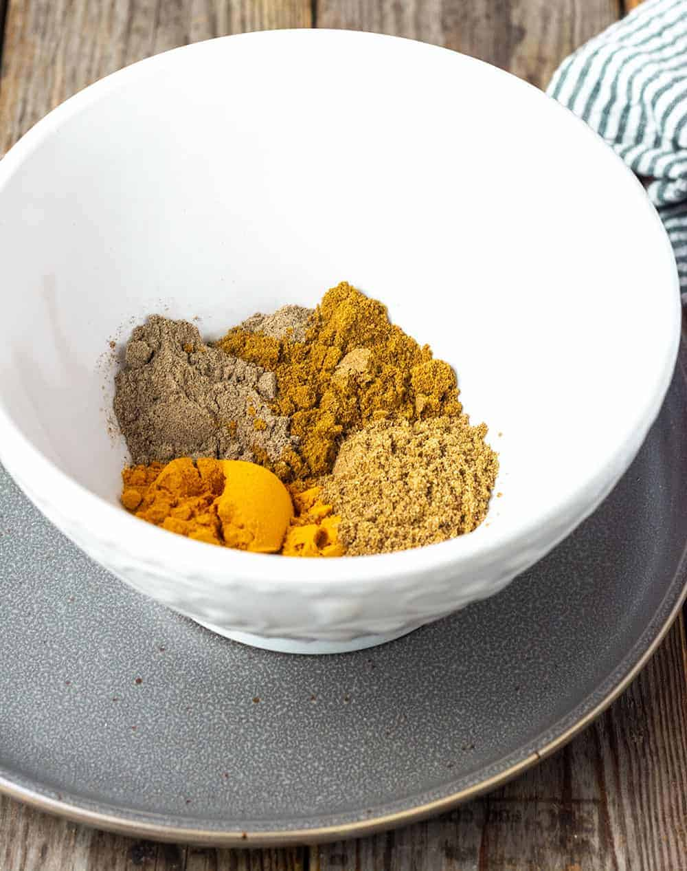 Curry powder ingredients in a white bowl, turmeric, coriander, cardamom and cumin in a white bowl