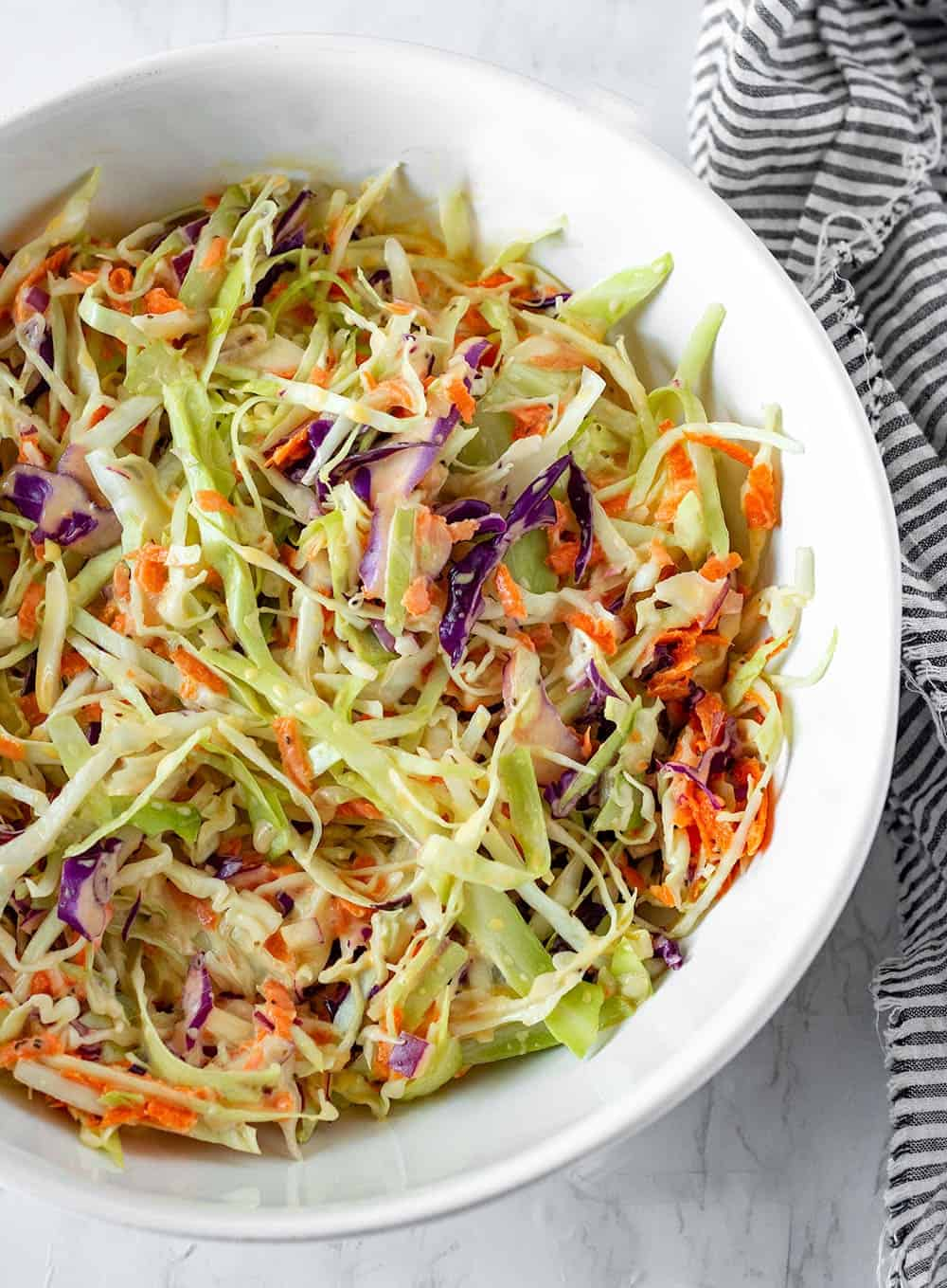 vegan coleslaw recipe with green cabbage, red cabbage, carrots shredded with a creamy vegan coleslaw dressing in a large white bowl