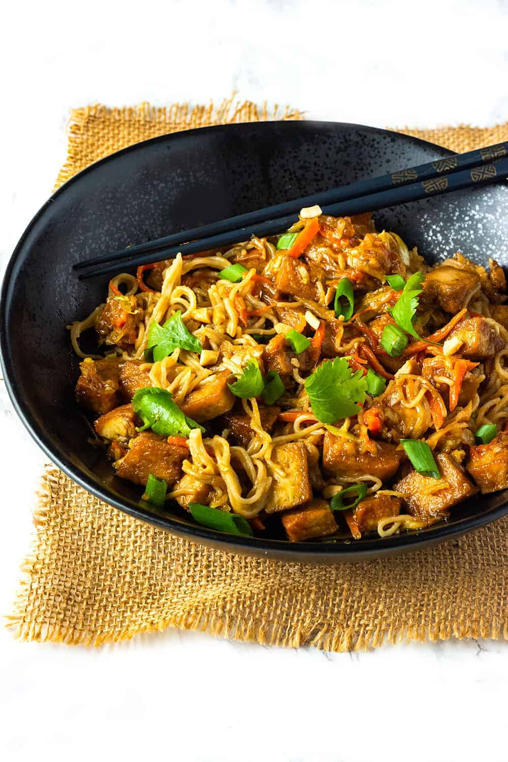 Easy peanut noodle with tofu, in a black bowl with peanuts, carrot, cabbage