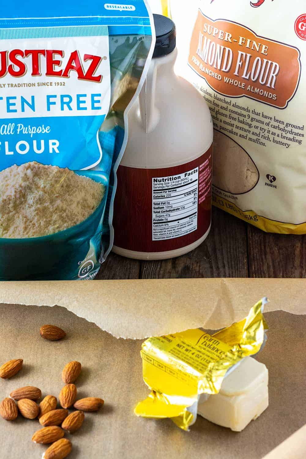 Vegan Gluten-Free Chinese almond cookies ingredients. bag of gluten-free flour, maple syrup bottle, bag of almond flour, raw almonds and Earth balance vegan buttery spread stick.