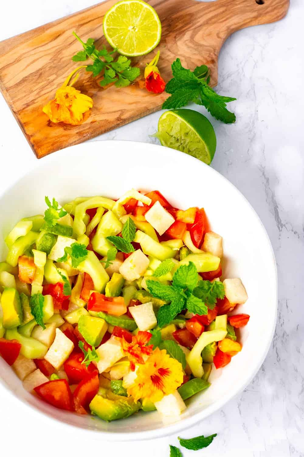 Jicama cucumber, tomato salad in a white bowl overlay
