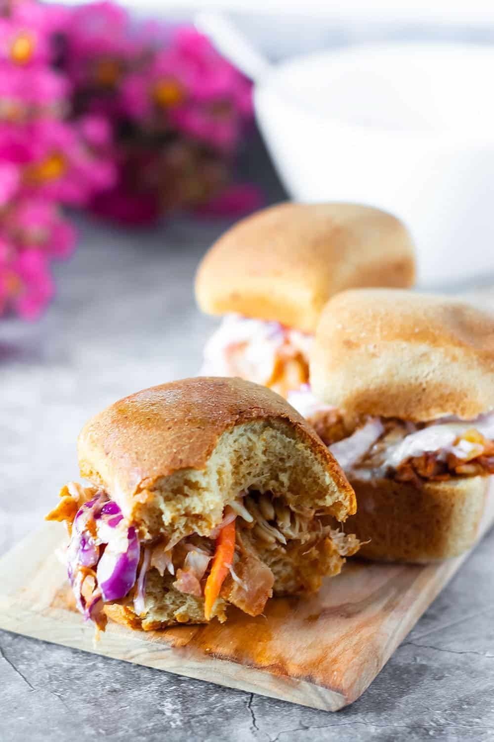 BBQ Jackfruit sandwiches, on a wooden cutting board, gluten free rolls topped with bbq jackfruit and coleslaw