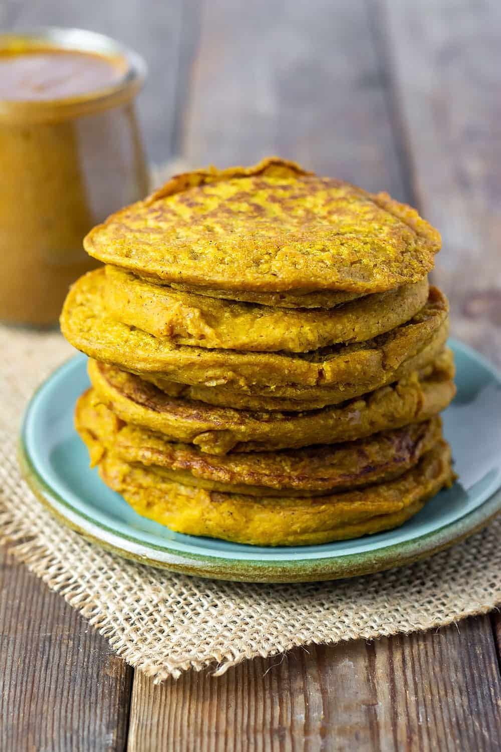 Vegan pumpkin pancakes stacked on a green plate