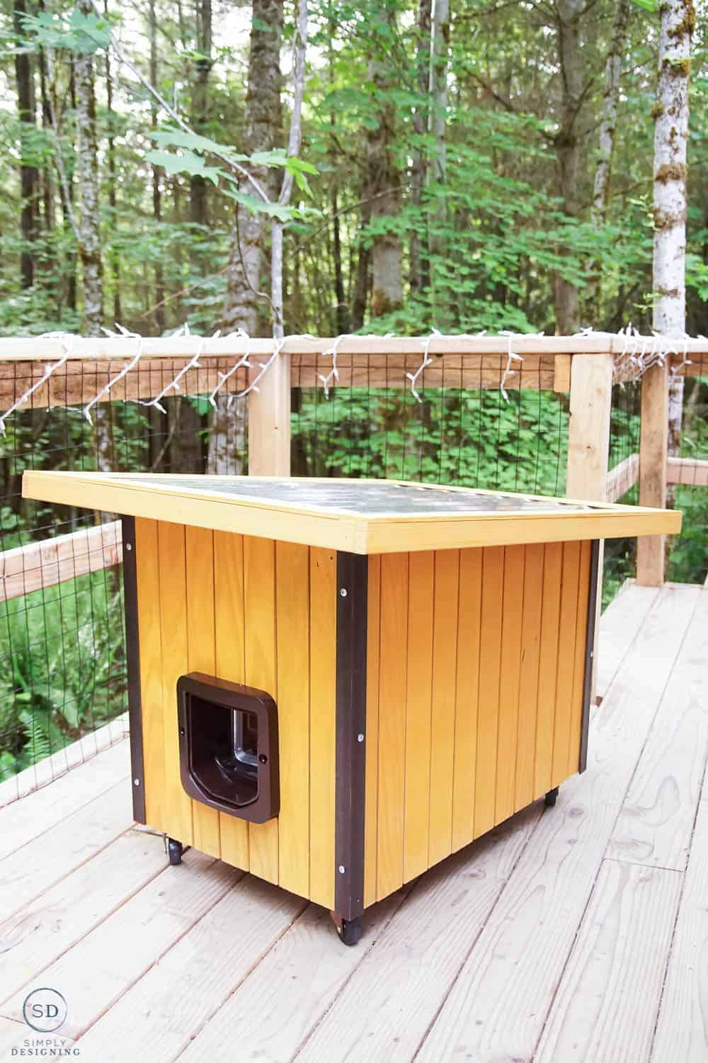 vertical photo of stained outdoor cat house with metal roof and angle iron on the sides