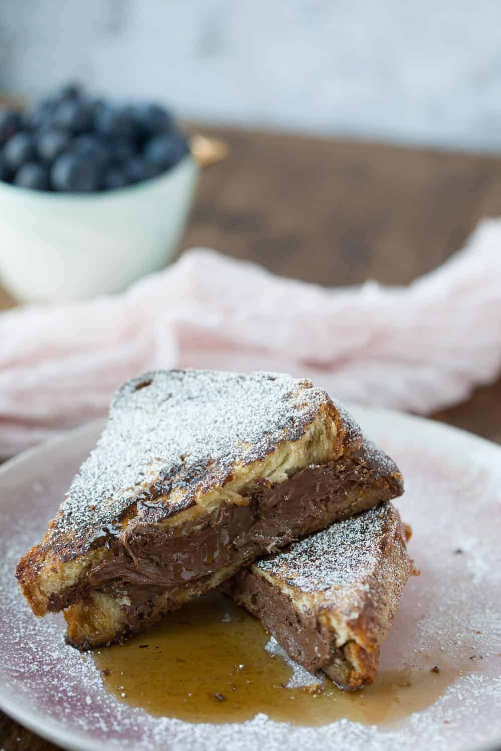 Two triangles of nutella Stuffed French toast on a plate with a bowl of blueberries in the background