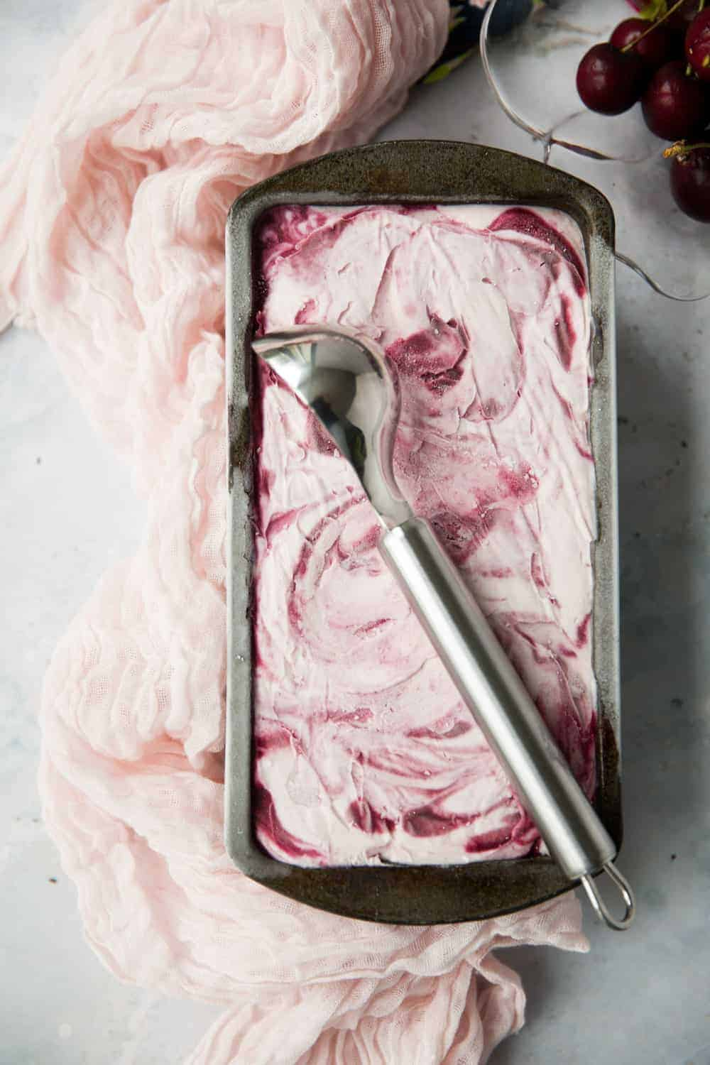 A loaf tin with black cherry ice cream inside. There is a silver ice cream scoop resting on top of the tin.