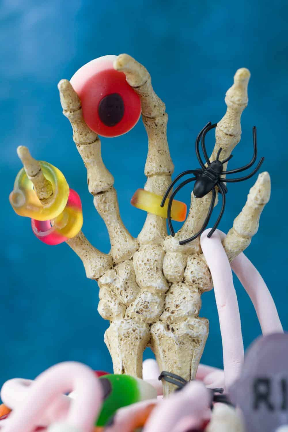 A skeleton hand with Halloween sweets draping from it.