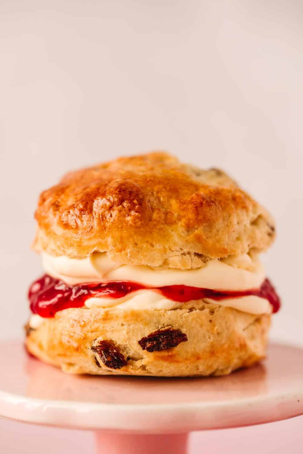 A fruit scone that has been cut in half and has strawberry jam and clotted cream spread on it.