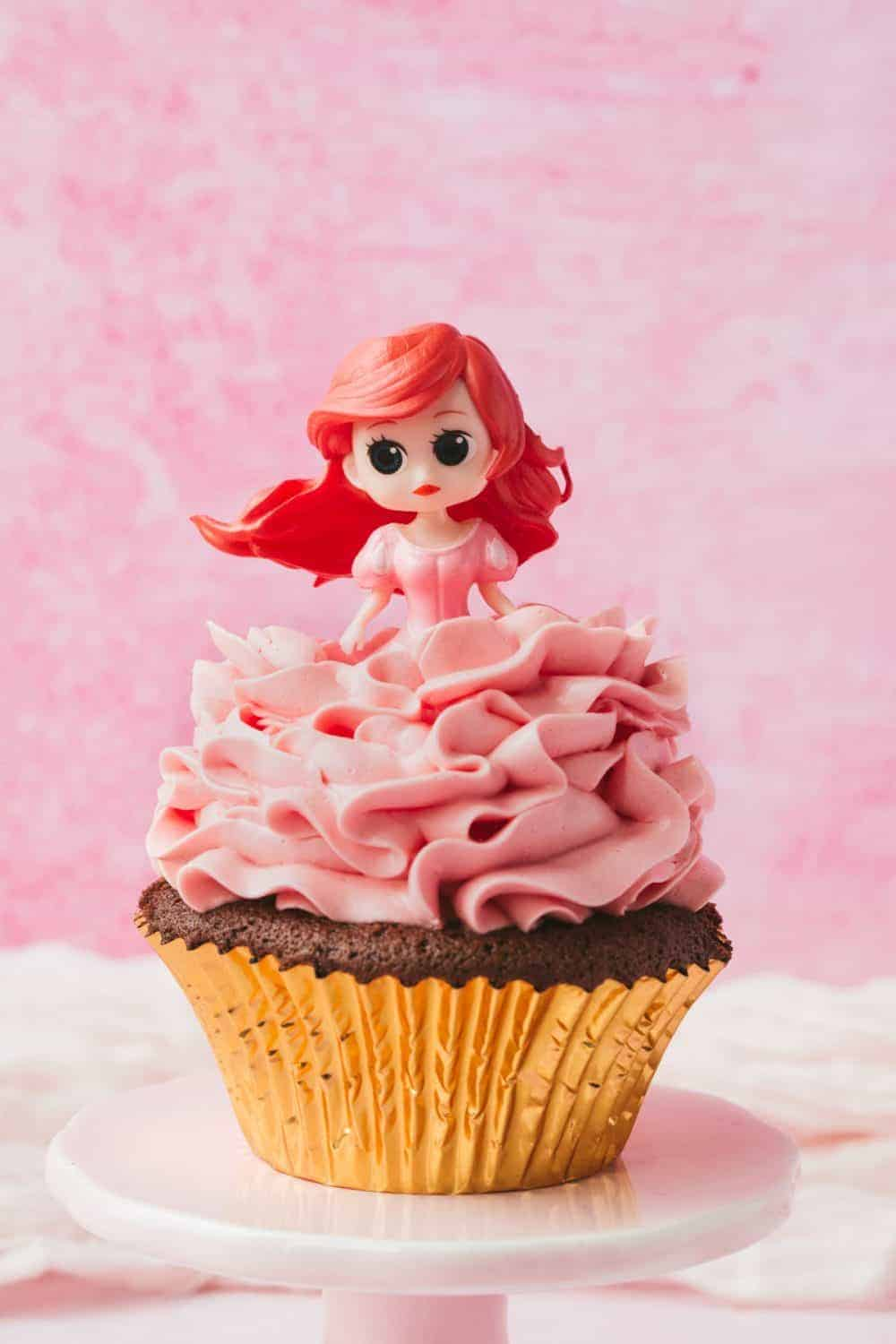 Disney princess Ariel on top of a chocolate cupcake covered in pink swiss meringue buttercream.
