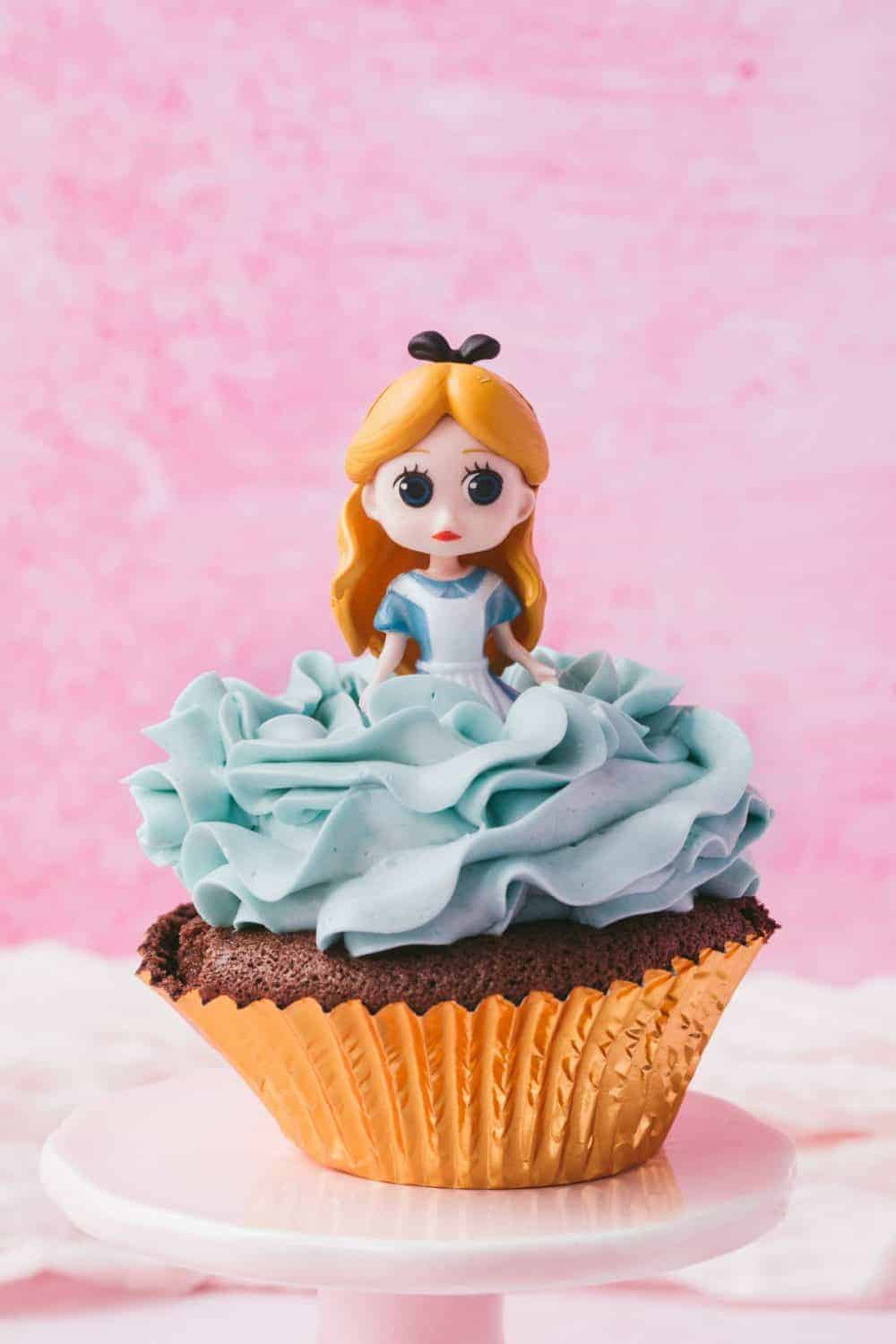 Alice in Wonderland cupcake topper on a chocolate cupcake with blue buttercream frosting.