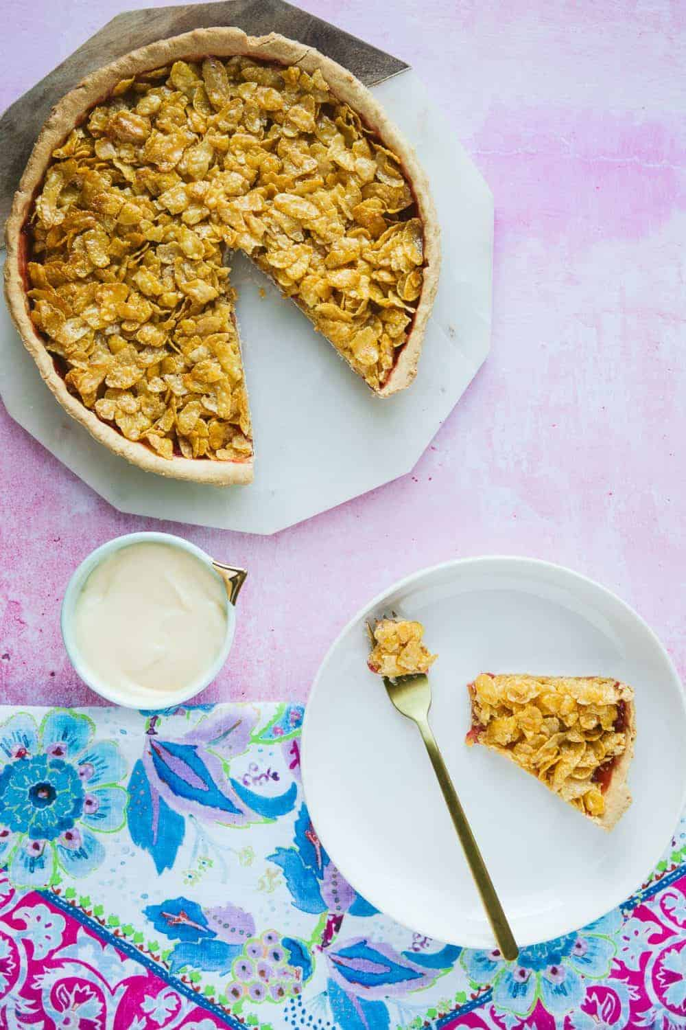 A cornflake tart with a slice cut out and a piece on a white plate beside a small pot of custard.