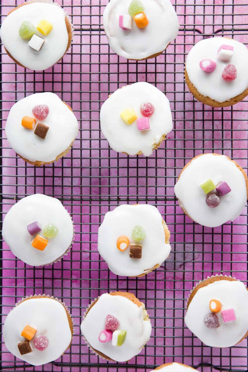 A cooling rack with fairy cakes on top of it.