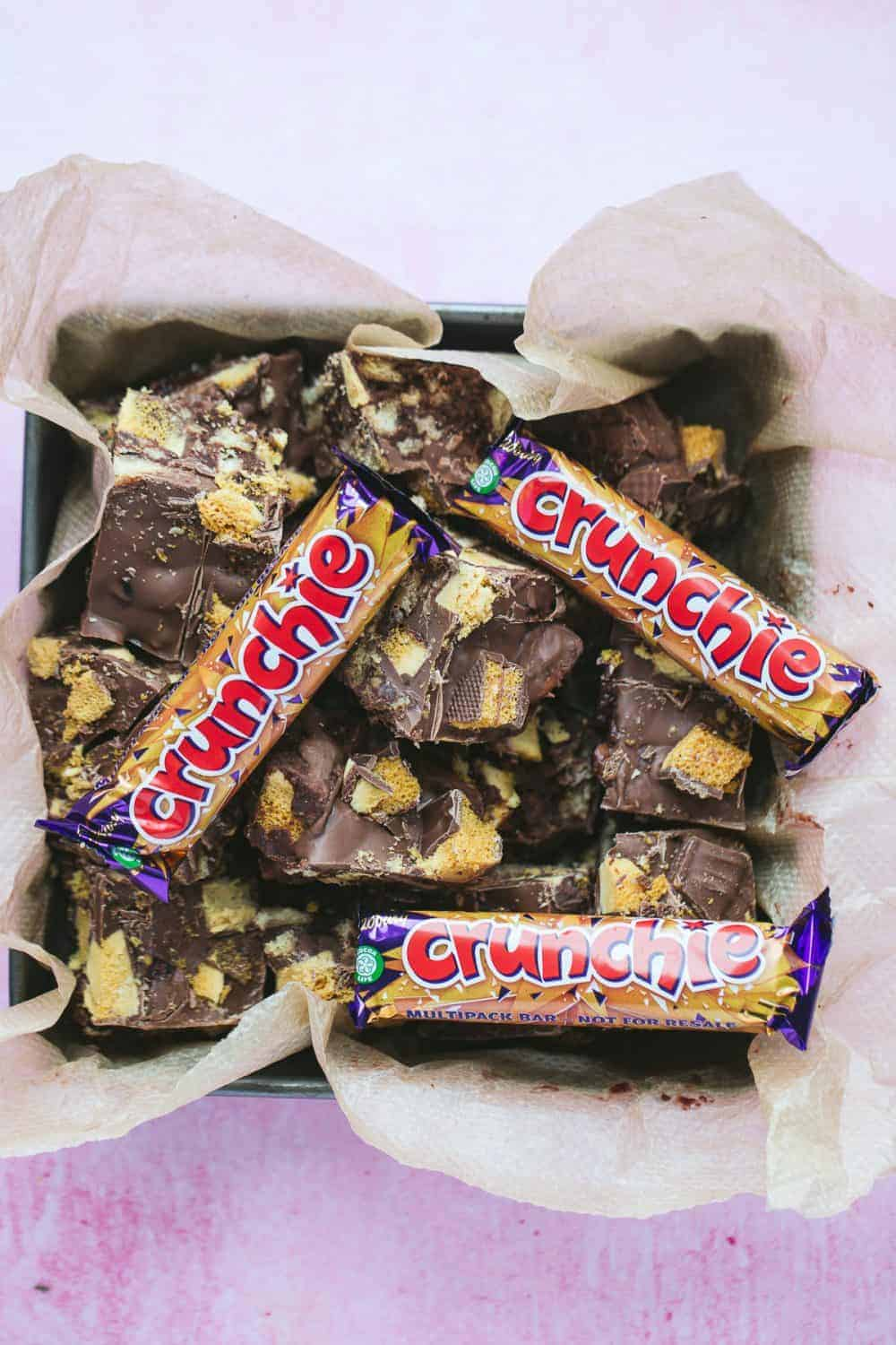 A baking tin filled with chocolate tiffin and Cadbury Crunchie bars.
