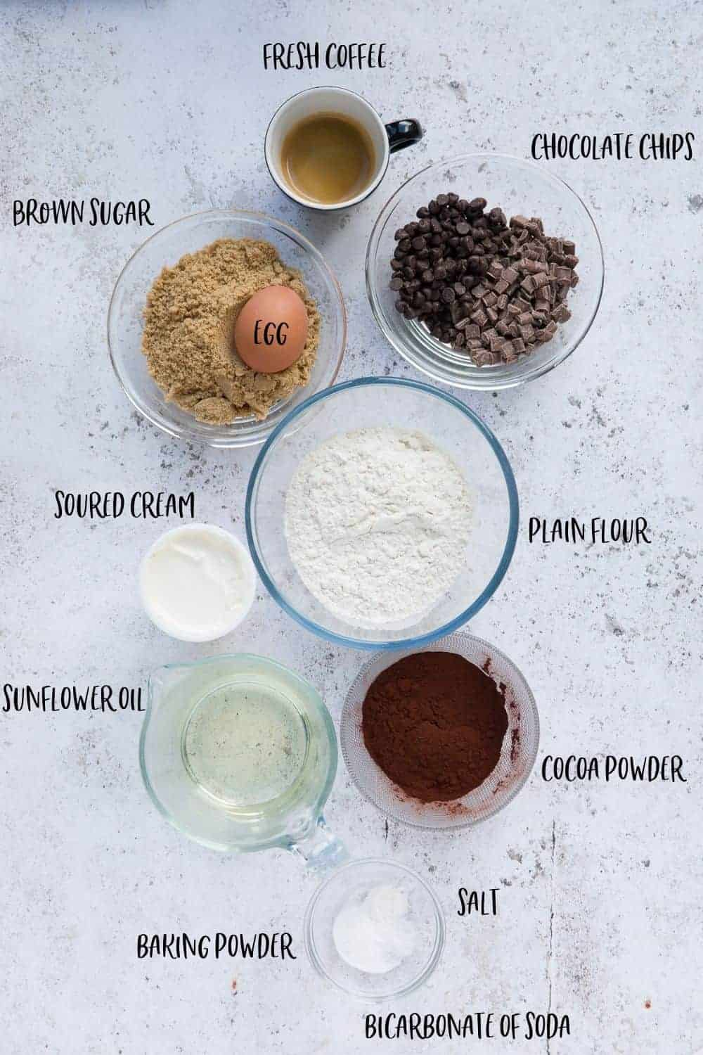 An image showing the following ingredients in glass bowls: fresh coffee, chocolate chips, brown sugar, egg, plain flour, soured cream, sunflower oil, cocoa powder, baking powder, salt and bicarbonate of soda.