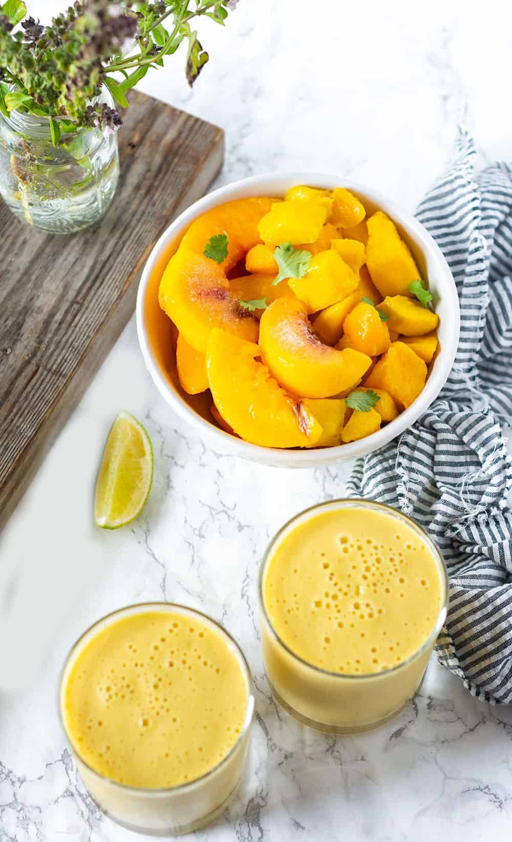 Peach Mango Smoothie overlay with mango peach fruits in a bowl