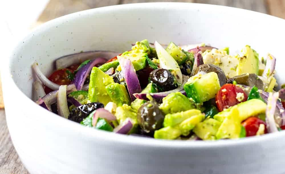 Close up vegan Greek salad with tomatoes, cucumber, red onions, avocado, olives in a white bowl