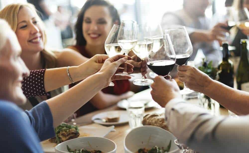diners toasting wine glasses in restaurant