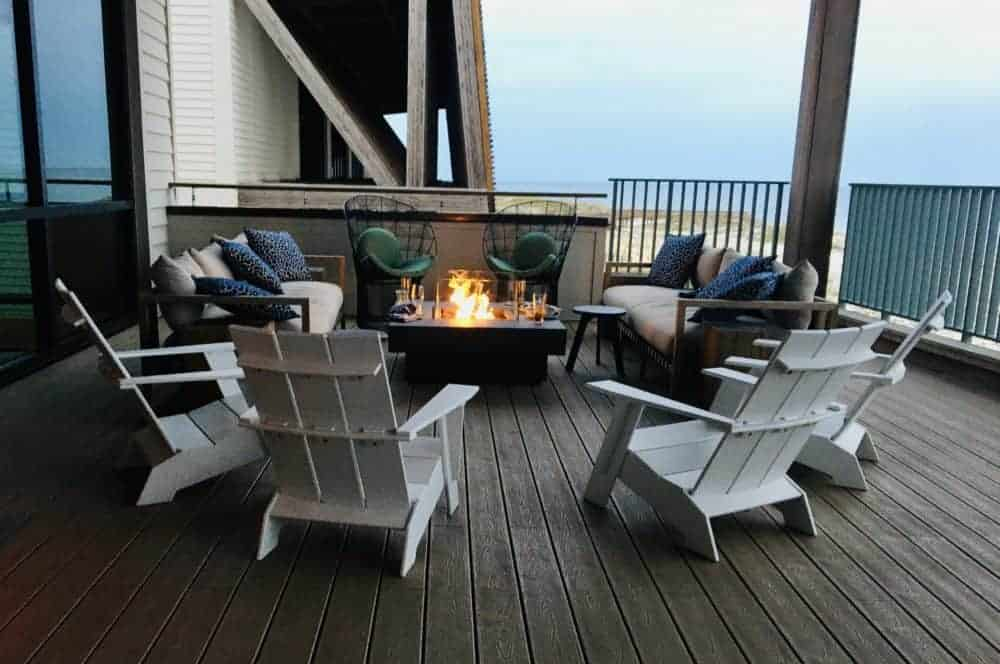 A fireplace and adirondack chairs on the deck outside of Perch at the Gulf State Park Lodge.