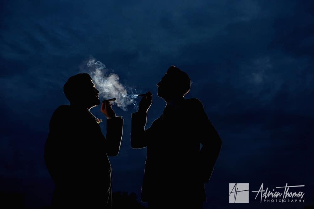 Groom and bestman smoking cigars