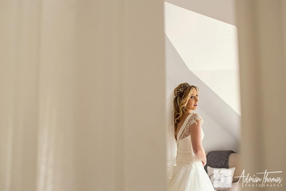 Photograph of bride looking in mirror before heading to New House Hotel Wedding Venue