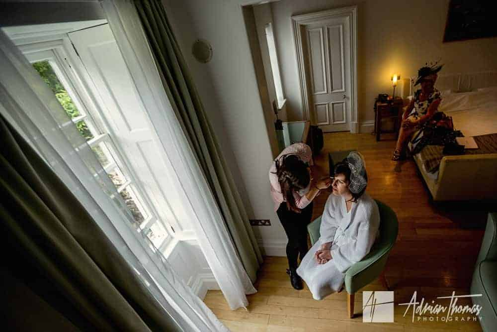 Bride having her makeup applied at Castell Deudraeth in Wedding at Portmeirion Village