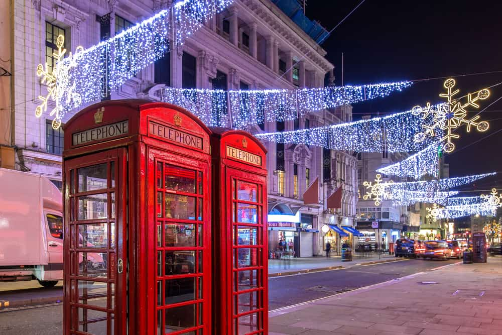 London highstreet with 2 red phone boxes and christmas lights