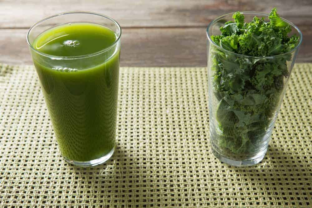 glass of kale juice and kale leaves in second glass