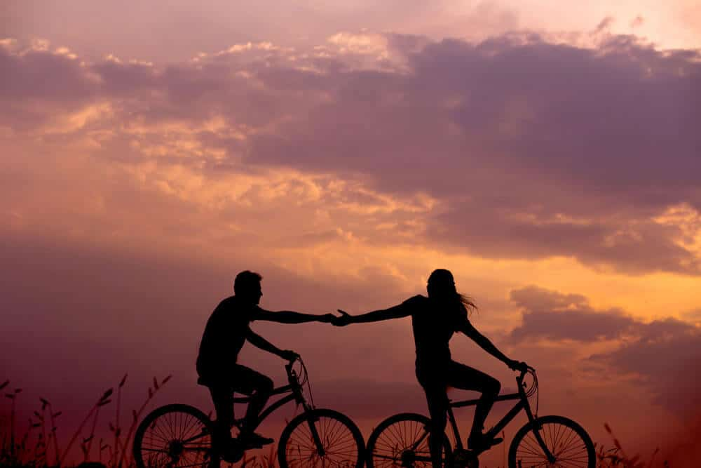 man and woman holding their hands while riding a bike