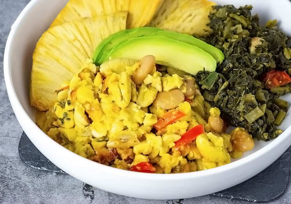 Ackee and butter beans served in a white bowl with roast breadfruit, callaloo and avocado