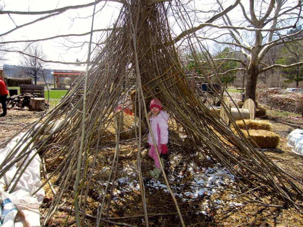 A girl plays in a teepee made of sticks at the ithaca childrens garden