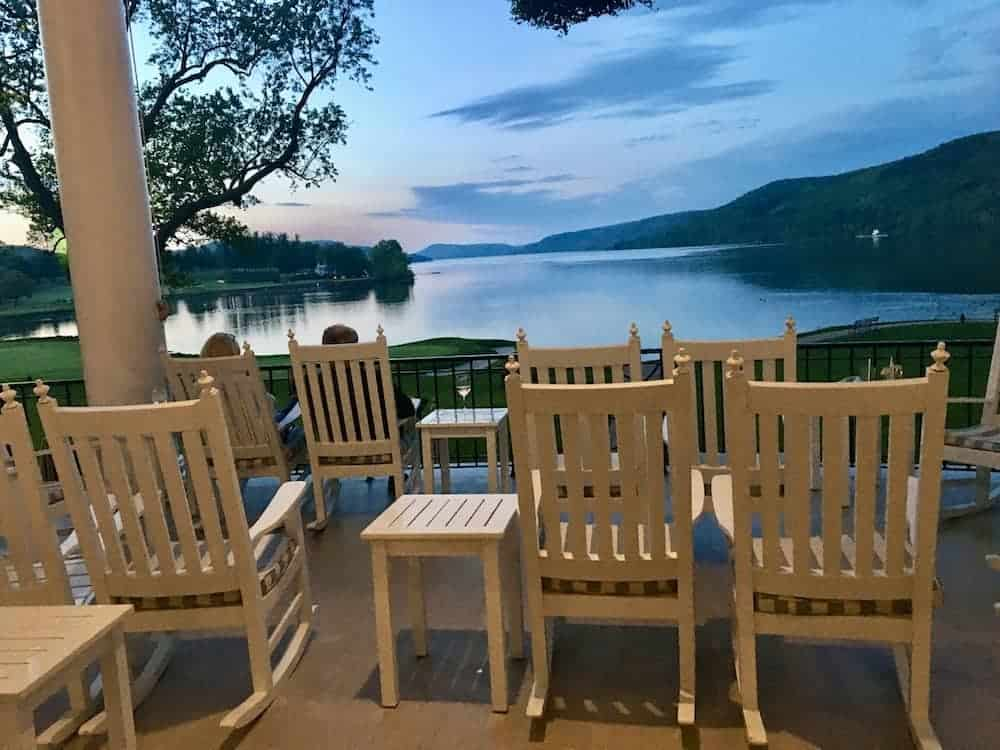 The view of Otesaga Lake at sunset from the rocking chairs on the porch of the Otesaga Resort.
