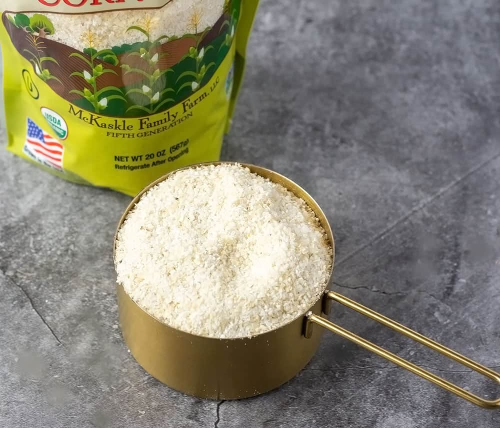 Grits in a gold measuring cup with a bag of grits in the background