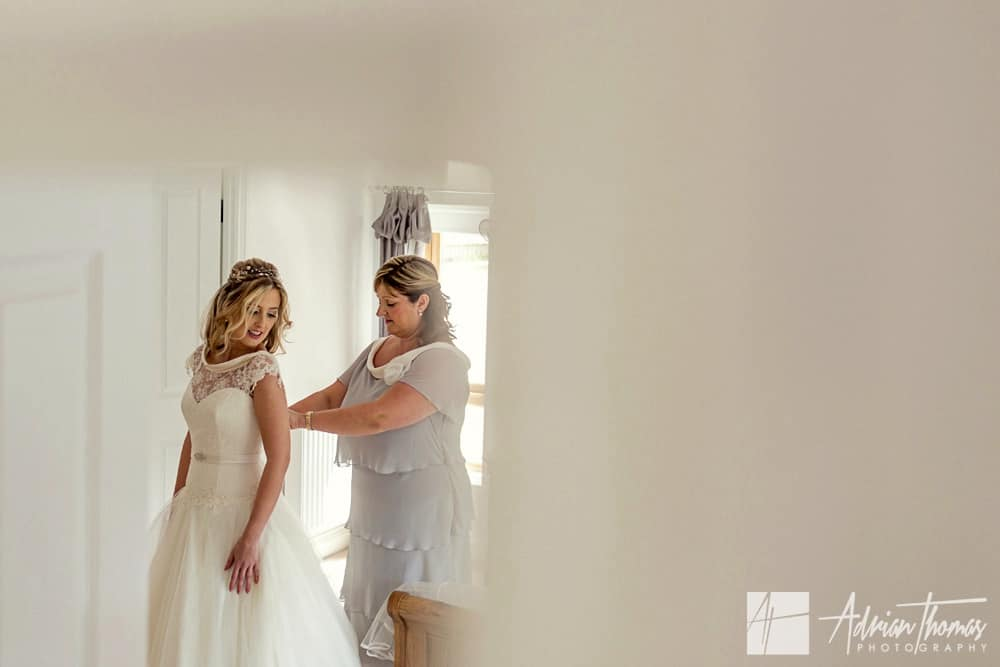 Mother of the bride helping bride get dressed