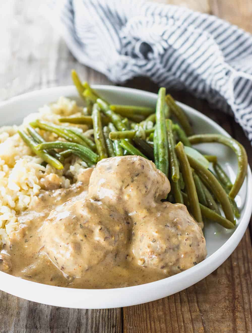 Lentil Meatballs smothered in cashew gravy with green beans and rice on a white plate