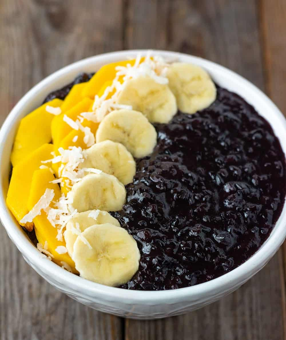 Easy black rice pudding, cooked with coconut milk, cinnamon, nutmeg and vanilla and sweetened with coconut sugar in a white bowl, topped with slices of banana, mango and coconut flakes on a wooden background