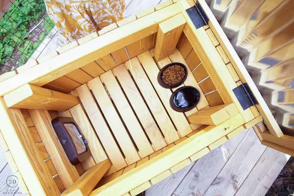looking inside the DIY cat house with black bowls of food and water in the bottom