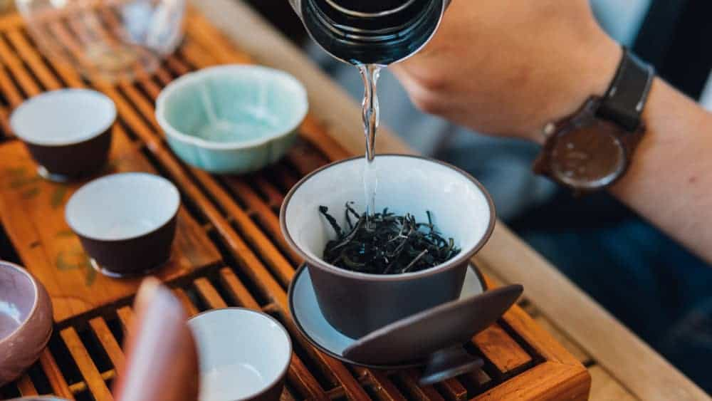 Brewing Chinese tea in ceramic gaiwan during the tea ceremony close-up. Gaiwan and other tea tools for the ceremony -